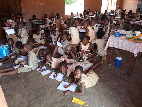 Des élèves s'asseyent au sol ou  se couchent pour prendre note dans une école publique à  l'EPP Adjagbo/ Crédit Photo : LT